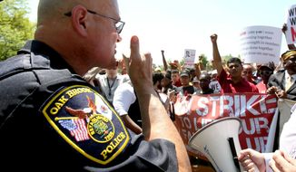 Oak Brook Police Commander Jeff Weber gives protesters a warning of arrest if they walk on the McDonald's property. Hundreds of protesters flooded the streets near the McDonald's Corp. headquarters in Oak Brook, Ill. Wednesday, May 21, 2014, railing about low wages and seeking $15 per hour for the rank and file. The Workers Organizing Committee of Chicago's Fight for 15 said in a statement that restaurant workers have held strikes and protests six times in the last 1 1/2 years challenging the company's median wage of $8.94. The Wednesday protest is a preview of what the group said it plans for Thursday's annual stockholder's meeting. The company closed one of its five buildings in anticipation of the protests.(AP Photo / Daily Herald, Bev Horne)