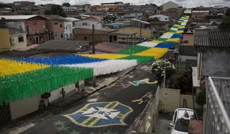A boy walks on a street decorated for the upcoming World Cup in Manaus, Brazil, Wednesday, May 21, 2014. Manaus is one of the host cities for the 2014 World Cup in Brazil. (AP Photo/Felipe Dana)
