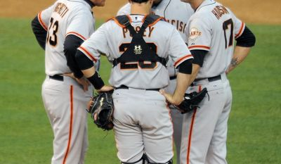 San Francisco Giants pitching coach Dave Righetti, left, catcher Buster Posey, center front, and third baseman Pablo Sandoval, center rear, talk with starting pitcher Tim Hudson, right, in the third inning of a baseball game against the Colorado Rockies on Thursday, May 22, 2014, in Denver. (AP Photo/Chris Schneider)