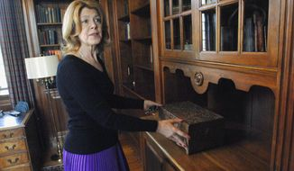 ADVANCE FOR USE SUNDAY, MAY 25 AND THEREAFTER - In this April 17, 2014 photo, curator Toni Tucker shows off a carved box by Emil Roth that is one of the original furnishings in Ewing Manor in Bloomington, Ill. The curator has been busy reinstalling furnishings that have been returned by the family to the historic landmark. (AP Photo/The Pantagraph, David Proeber)