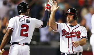 Atlanta Braves second baseman Dan Uggla, right,  celebrates with teammate B.J. Upton, left, after scoring on a Ryan Doumit base hit in the seventh inning of a baseball game  against Milwaukee Brewers Thursday, May 22, 2014 in Atlanta. (AP Photo/John Bazemore)