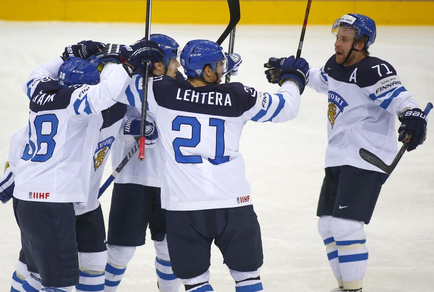 Finland's players celebrate after Olli Palola scored against Canada during the Group A Quarterfinal match at the Ice Hockey World Championship in Minsk, Belarus, Thursday, May 22, 2014. (AP Photo/Sergei Grits)