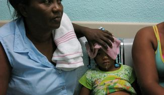 In this May 15, 2014 photo, five-year-old Karla Sepulveda, who suffers chikungunya fever symptoms, waits with her grandmother for treatment in the pediatric area of a public hospital in the coastal town of Boca Chica, Dominican Republic. The mosquito-born virus, common in Africa and Asia, arrived to the Caribbean in late 2013 and has affected more than 10,000 people in the Dominican Republic. (AP Photo/Ezequiel Abiu Lopez)
