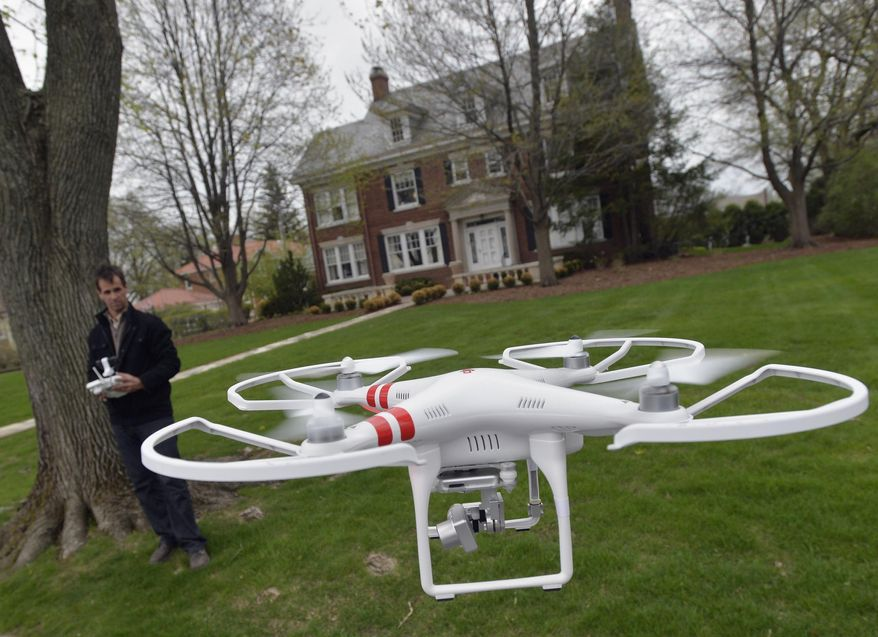 ** FILE **  A man demonstrates the use of a drone in Peoria, Ill., April 29, 2014. (Associated Press)