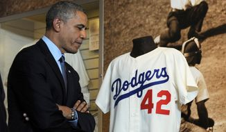 President Obama looks at Jackie Robinson's Brooklyn Dodgers memorabilia during a tour of the Baseball Hall of Fame in Cooperstown, New York. Mr. Obama visited the museum to highlight tourism and to help spur international visits to the 50 states. (Associated Press)
