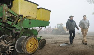 Le Sueur County, Minn. farmer Bob Braun, left, and farming partner Ryan Thelemann walk past a planter idled by wet weather  in Le Sueur, Minn., on Tuesday, May 20, 2014. Wet weather has delayed spring planting for many farmers in Minnesota, threatening yields andcrop insurance benefits.  (AP Photo/The Mankato Free Press, John Cross)