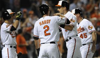 Baltimore Orioles' Ryan Flaherty, center right, is congratulated by teammates, left to right, David Lough, J.J. Hardy, and Steve Clevenger after hitting a three-run home run against the Cleveland Indians in the sixth inning of a baseball game Thursday, May 22, 2014, in Baltimore. (AP Photo/Gail Burton)