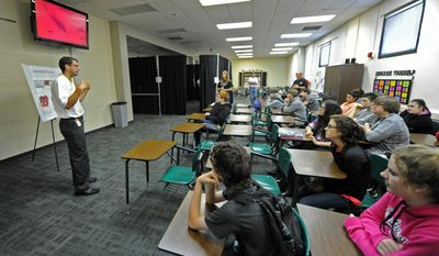 In this Friday May 16, 2014, photo, Cummins engineer Mike Hughes, left, talks with eighth grade students at Greenwood Middle Schoot about the virtual reality computer-aided drafting system being demonstrated on the screen behind him in Greenwood, Ind.  (AP Photo/The Daily Journal, Scott Roberson)
