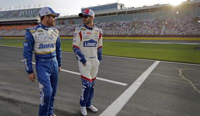 Jimmie Johnson, right, and Brian Vickers, left, walk down pit road before qualifying for Sunday's NASCAR Sprint Cup series auto race at Charlotte Motor Speedway in Concord, N.C., Thursday, May 22, 2014. (AP Photo/Chuck Burton)