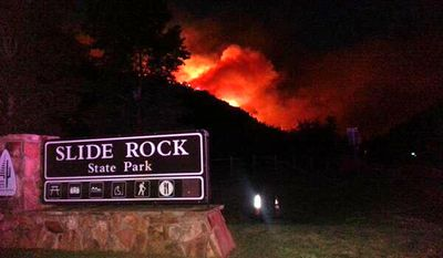 In this photo released by the Arizona Department of Public Safety, flames from a wildfire rise over a ridge behind the popular Slide Rock State Park Oak Creek Canyon near Sedona, Ariz., Tuesday, May 20, 2014. About 200 firefighters and other personnel are already assigned to the 450-acre Slide Fire, including five Hotshot crews, Coconino National Forest officials said Wednesday. (AP Photo/Arizona Department of Public Safety, Carrick Cook)
