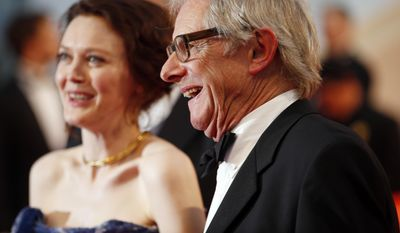 Director Ken Loach, right, and actress Simone Kirby leave following the screening of Jimmy's Hall at the 67th international film festival, Cannes, southern France, Thursday, May 22, 2014. (AP Photo/Alastair Grant)