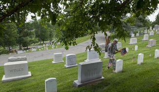 """A soldier of the 3rd U.S. Infantry Regiment, also known as The Old Guard, places flags at grave sites at Arlington National Cemetery in Arlington, Va., Thursday, May 22, 2014, as part of the annual """"Flags-In"""" ceremony in preparation for Memorial Day. (AP Photo/Cliff Owen)"""