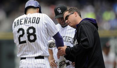 Colorado Rockies trainer Keith Dugger, right, and manager Walt Weiss, center, look at the elbow of Nolan Arenado after he was hit by a pitch in the first inning of a baseball game against the San Francisco Giants on Thursday, May 22, 2014, in Denver. (AP Photo/Chris Schneider)