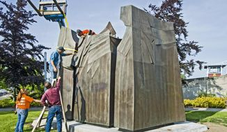 The installation crew discusses how to attach two sections of Sun King, a bronze sculpture, in a small park near the Thea Foss Waterway, on Wednesday, May 21, 2014 in Tacoma, Wash.  The first major piece of public art commissioned by the city has been out of public view since 2006.  (AP Photo/The News Tribune, Peter Haley)