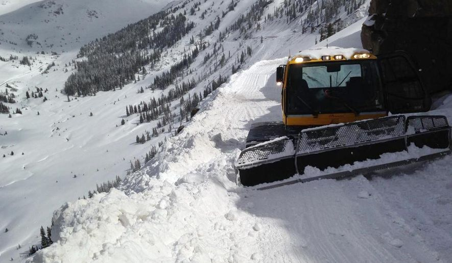 This recent photo provided the Colorado Dept. of Transportation shows a plow clearing snow on Independence Pass, which connects Aspen with Twin Lakes, in Colorado. On Thursday May 22, 2014 CDOT reopened the pass, which had up to 12 feet of snow in some spots. (AP Photo/Colorado Dept. of Transportation)