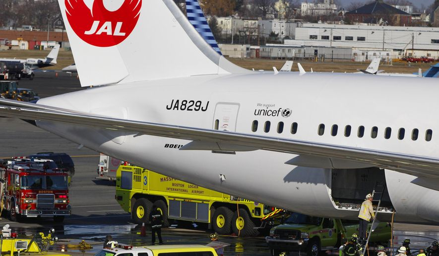 In this Jan. 7, 2013, file photo, a Japan Airlines Boeing 787 jet aircraft is surrounded by emergency vehicles while parked at a Terminal E gate at Logan International Airport in Boston as a fire chief looks into the cargo hold. (AP Photo/Stephan Savoia, File)