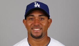 "In a 2014 photo, Miguel Olivo of the Los Angeles Dodgers poses for a photo in Glendale, Ariz. Olivo has been suspended by the Dodgers' top farm team following his fight in the dugout with Triple-A Albuquerque teammate Alex Guerrero. In a statement released Wednesday night, May 21, 2014,the Dodgers say Olivo was placed on the suspended list by the Albuquerque Isotopes. The veteran catcher is on the Dodgers' 40-man roster, and the club says he ""will remain suspended pending the completion of an investigation"" into the brawl during Tuesday's game at Salt Lake. (AP Photo/Paul Sancya)"
