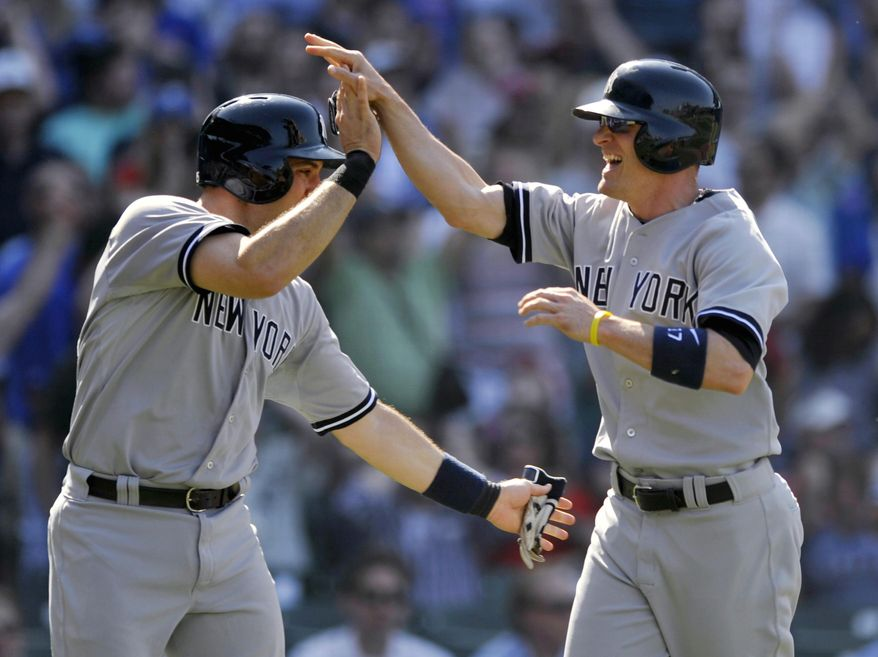 New York Yankees' Brendan Ryan right, celebrates with Mark Teixeria at home plate after both scored on a ball hit by Ichiro Suzuki during the ninth inning of an interleague baseball game against the Chicago Cubs in Chicago, Wednesday, May 21, 2014. (AP Photo/Paul Beaty)