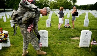 Army Pfc. Tristan Evans with the Third U.S. Infantry Regiment (The Old Guard) places a small American flag at a grave marker at Section 60 to honor the nations fallen members of the military at Arlington National Cemetary as Coleen Bowman of Old Town Alexandria, Va., right, visits the grave of her husband, Army Sgt. Maj. Robert Bowman who died of cancer after serving in Iraq, with her friend Tanya Callaghan-McCann, center, Washington, D.C, Thursday, May 22, 2014. The Old Guard placed flags for more than 220,000 graves. (Andrew Harnik/The Washington Times)