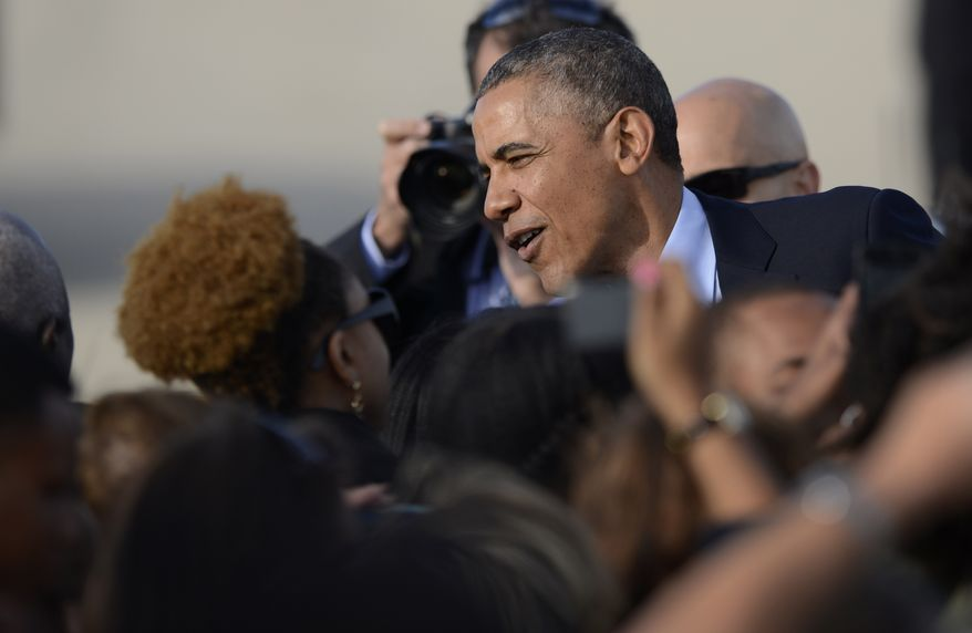 President Barack Obama greets a small crowd of supporters after arriving at O'Hare International Airport in Chicago, Thursday, May 22, 2014. (AP Photo/Paul Beaty)