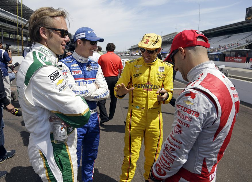 Helio Castroneves, of Brazil, right center, tells a story to fellow drivers Ed Carpenter, left, Ryan Briscoe, of Australia, left center, and Tony Kanaan, of Brazil, before the start of practice for the Indianapolis 500 IndyCar auto race at the Indianapolis Motor Speedway in Indianapolis, Monday, May 19, 2014. (AP Photo/Michael Conroy)