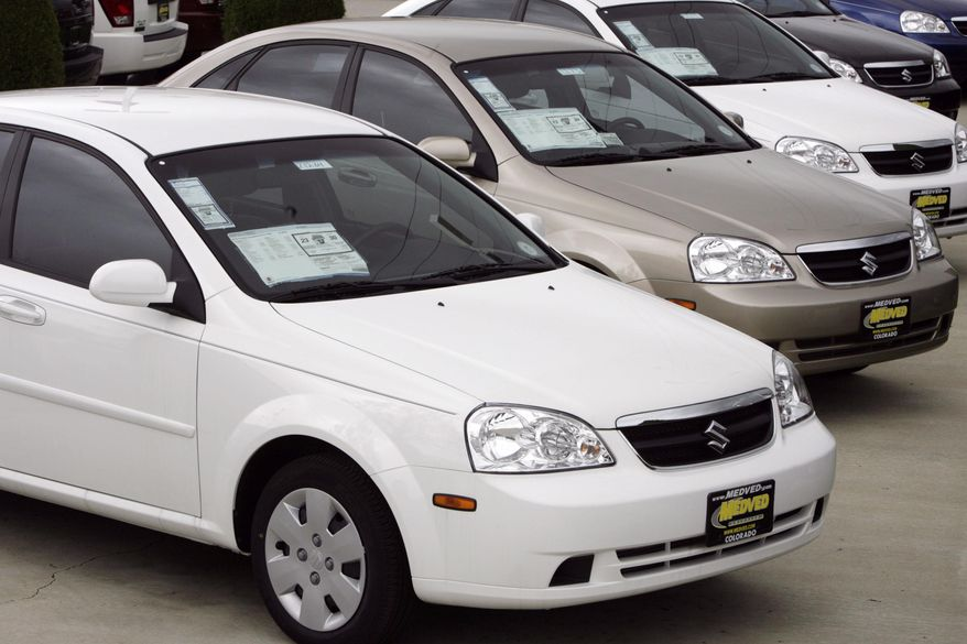FILE - This May 6, 2007 file photo shows unsold 2007 Forenza sedans outside a Suzuki dealership in the northwest Denver suburb of Wheat Ridge, Colo. Suzuki is recalling more than 184,000 small cars in the U.S. because the steering columns can catch fire. The recall covers Forenza models from 2004 through 2008 and Reno models from 2005 through 2008. Both vehicles were made for Suzuki by General Motors. (AP Photo/David Zalubowski)