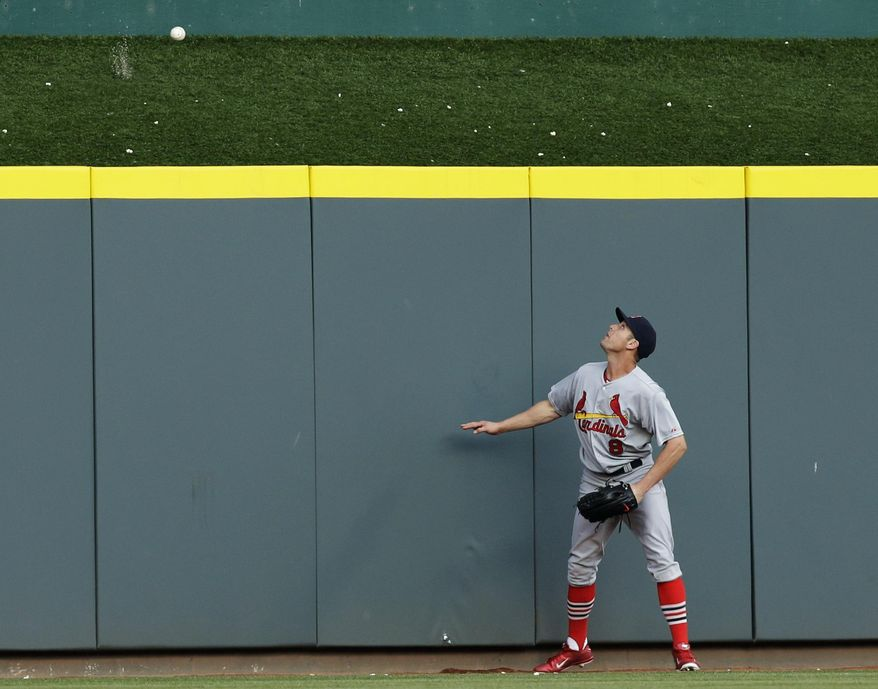 St. Louis Cardinals' Peter Bourjos watches a three-run home run hit by Cincinnati Reds' Todd Frazier in the third inning of a baseball game, Friday, May 23, 2014, in Cincinnati. (AP Photo/Al Behrman)