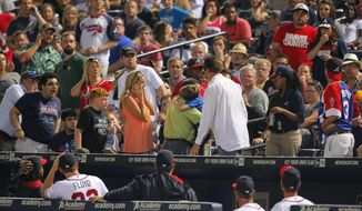"In this Tuesday, May 20, 2014 photo, Atlanta Braves players and fans react as a young boy is picked up by his father and rushed up the steps after being hit by a foul ball off the bat of Milwaukee Brewers' Carlos Gomez in the seventh inning of a baseball game against the Atlanta Braves in Atlanta. The 8-year-old boy who was struck in the head has been released from the hospital and is ""doing well.""  While the family requested privacy and boy's name was not released, the Braves said Thursday they had received a call from the victim. He thanked the players who visited him in the hospital and let the team ""know that he's home and doing well.""  (AP Photo/Todd Kirkland)"