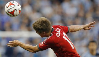 Toronto FC defender Nick Hagglund heads the ball during the first half of an MLS soccer match against Sporting Kansas City in Kansas City, Kan., Friday, May 23, 2014. (AP Photo/Orlin Wagner)