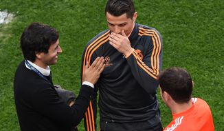 Former Real player Raul Gonzalez, left, laughs with Real's Cristiano Ronaldo, centre, and Real goalkeeper Iker Casillas, during a training session ahead of Saturday's Champions League final soccer match between Real Madrid and Atletico Madrid, in Luz stadium in Lisbon, Portugal, Friday, May 23, 2014. (AP Photo/Paulo Duarte)