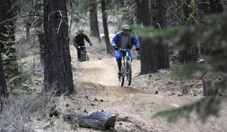 In this May 6, 2014 photo, a pair of mountain bike riders make their way down Whoops Trail near Bend, Ore. (AP Photo/The Bulletin, Ryan Brennecke)