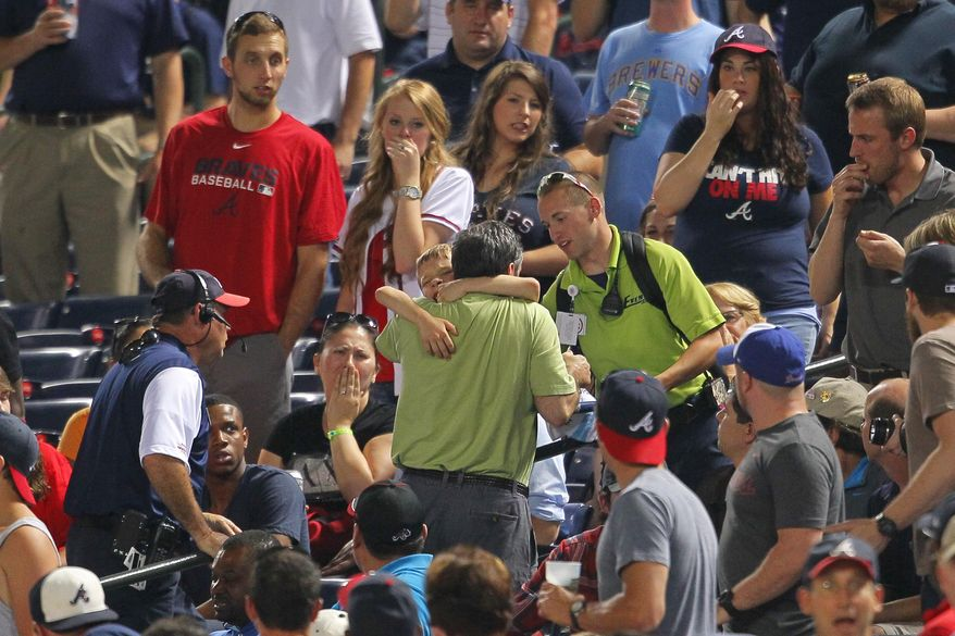 "In this Tuesday, May 20, 2014 photo, fans react as a young boy is picked up by his father and rushed up the steps after being hit by a foul ball off the bat of Milwaukee Brewers' Carlos Gomez in the seventh inning of a baseball game against the Atlanta Braves in Atlanta. The 8-year-old boy who was struck in the head has been released from the hospital and is ""doing well.""  While the family requested privacy and boy's name was not released, the Braves said Thursday they had received a call from the victim. He thanked the players who visited him in the hospital and let the team ""know that he's home and doing well.""  (AP Photo/Todd Kirkland)"
