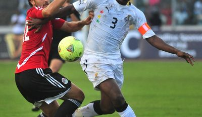 FILE - In this Oct. 15, 2013, file photo, Ghana captain Asamoah Gyan, right, is challenged by Egypt's Hossam Ghaly during their World Cup playoff soccer match in Kumasi, Ghana. (AP Photo, File) - SEE FURTHER WORLD CUP CONTENT AT APIMAGES.COM