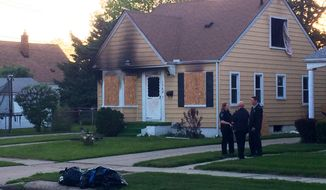Authorities gather at the scene of a house fire under investigation on North Altadena Avenue in Royal Oak on Friday, May 23, 2014. The fire that left one person dead early this morning is under investigation, officials said. (AP Photo/Detroit Free Press, Robert Allen)