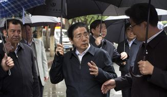 China's Public Security Minister Guo Shengkun, center, talks with Xinjiang Party Secretary Zhang Chunxian, right, as they visit the site of an explosion in Urumqi, northwest China's Xinjiang region, Thursday, May 22, 2014. Assailants in two SUVs plowed through shoppers while setting off explosives on a busy street market in China's volatile northwestern region of Xinjiang on Thursday, the local officials said, killing over two dozen people and injuring more than 90. The attack was the bloodiest in a series of violent incidents that Chinese authorities have blamed on radical separatists from the country's Muslim Uighur minority. (AP Photo/Andy Wong)