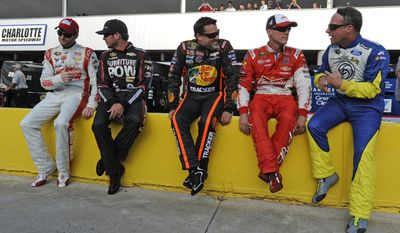Dale Earnhardt Jr, Martin Truex Jr., Tony Stewart, Kevin Harvick and Dave Blaney, from left, chat as they sit on pit wall before qualifying for Sunday's NASCAR Sprint Cup series auto race at Charlotte Motor Speedway in Concord, N.C., Thursday, May 22, 2014. (AP Photo/Mike McCarn)