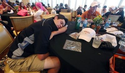 Texas golfer Beau Hossler rests during a rain delay in the first round of the NCAA men's golf championship Friday, May 23, 2014, at Prairie Dunes Country Club in Hutchinson, Kan. (AP Photo/The Hutchinson News, Travis Morisse)
