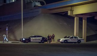In this photo taken on Thursday, May 22, 2014, Albuquerque police officers investigate the scene underneath the Interstate 40 overpass on 2nd Street where police shot and killed a knife-wielding man in Albuquerque, N.M. Police said Friday, May, 23, 2014, the man, indentified as Ralph Chavez, yelled at officers to shoot him after he allegedly attacked a woman believed to be his girlfriend and then slashed the throat of a man who tried to help her. (AP Photo/The Albuquerque Journal, Roberto Rosales)