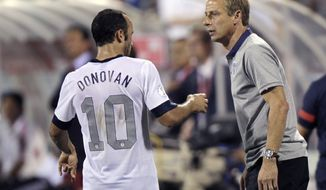 In this photo taken Tuesday, Sept. 10, 2013, United States manager Jurgen Klinsmann, right, talks with Landon Donovan during a World Cup qualifying soccer match against Mexico in Columbus, Ohio. The United States clinched its seventh straight World Cup appearance, getting second-half goals from Eddie Johnson and Donovan on Tuesday night in a 2-0 win over Mexico.(AP Photo/Jay LaPrete)
