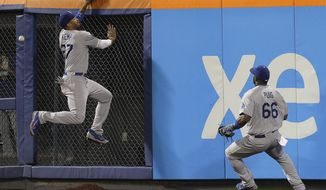 Los Angeles Dodgers center fielder Matt Kemp (27) leaps unsuccessfully for a ball hit by New York Mets' Curtis Granderson as right fielder Yasiel Puig watches during the eighth inning of a baseball game, Thursday, May 22, 2014, in New York. David Wright scored on the play. (AP Photo/Julie Jacobson)