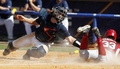 Arkansas' Krisjon Wilkerson (33) beats the tag from Mississippi's Will Allen as he slides into home plate during the fourth inning at the Southeastern Conference NCAA college baseball tournament on Friday, May 23, 2014, in Hoover, Ala. (AP Photo/Butch Dill)