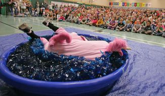 North Pole Elementary School principal Mark Winford holds true to his promise of dressing like a unicorn and jumping into a kiddie pool holding 140 gallons of gelatin to reward his students for reaching their reading points goal of 24,000 Thursday, afternoon, May 22, 2014 in the school gymnasium in North Pole, Alaska. The reading points are based on comprehension quiz scores the kids took after reading books. The students read over 35,000 books, compiling 24,793 points. (AP Photo/Fairbanks Daily News-Miner, Eric Engman)