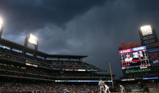 A dark cloud is seen over Citizens Bank Park as Philadelphia Phillies starting pitcher Roberto Hernandez throws before play was suspended due to rain during the fourth inning of a baseball game against the Los Angeles Dodgers, Friday, May 23, 2014, in Philadelphia. (AP Photo/Matt Slocum)