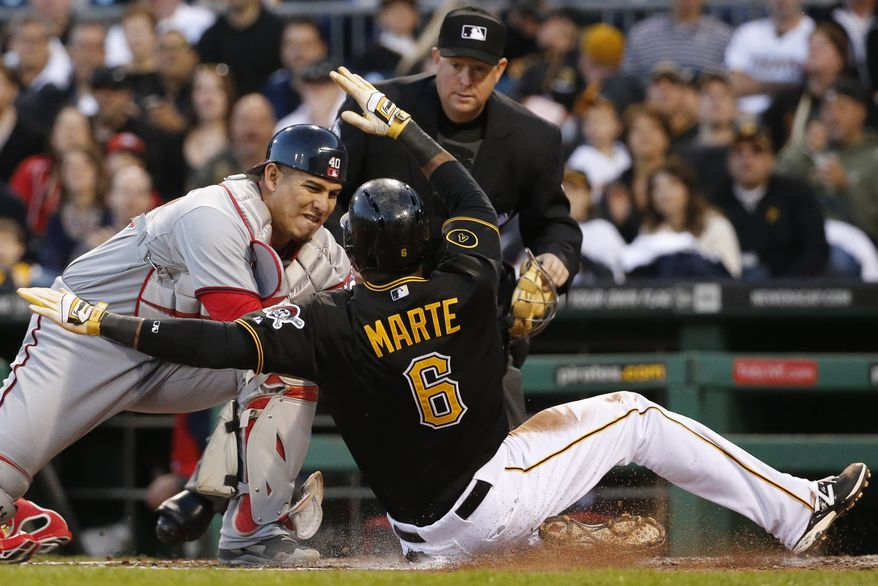 Washington Nationals catcher Wilson Ramos tags out Pittsburgh Pirates' Starling Marte (6) attempting to score on a squeeze bunt by Pirates pitcher Charlie Morton during the fourth inning of a baseball game in Pittsburgh Friday, May 23, 2014. Watching the play is umpire Todd Tichenor. (AP Photo/Gene J. Puskar)