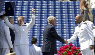 A United States Naval Academy midshipman reacts after receiving her diploma as Secretary of Defense Chuck Hagel shakes hands with a midshipman during the United States Naval Academy 2014 Class academy's graduation and commissioning ceremonies at Navy-Marine Corps Stadium in Annapolis,  Md., Friday, May 23, 2014. (AP Photo/Jose Luis Magana)