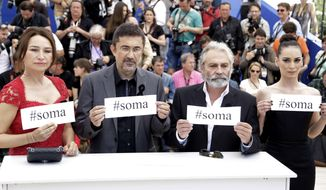 "FILE - In this Friday, May 16, 2014 file photo, from left, actress Demet Akbag, director Nuri Bilgle Ceylan, actor Haluk Bilginer and actress Melisa Soezen pose for photographers with signs reading ""soma"", a reference to Turkey's worst mining incident in which hundreds of miners were killed earlier in the week in Soma, Turkey, during a photo call for Winter Sleep at the 67th international film festival, Cannes, southern France. (AP Photo/Thibault Camus)"