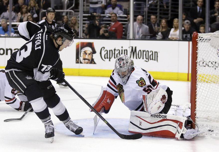 Los Angeles Kings center Tyler Toffoli, left, scores past Chicago Blackhawks goalie Corey Crawford during the second period of Game 3 of the Western Conference finals of the NHL hockey Stanley Cup playoffs in Los Angeles, Saturday, May 24, 2014. (AP Photo/Chris Carlson)