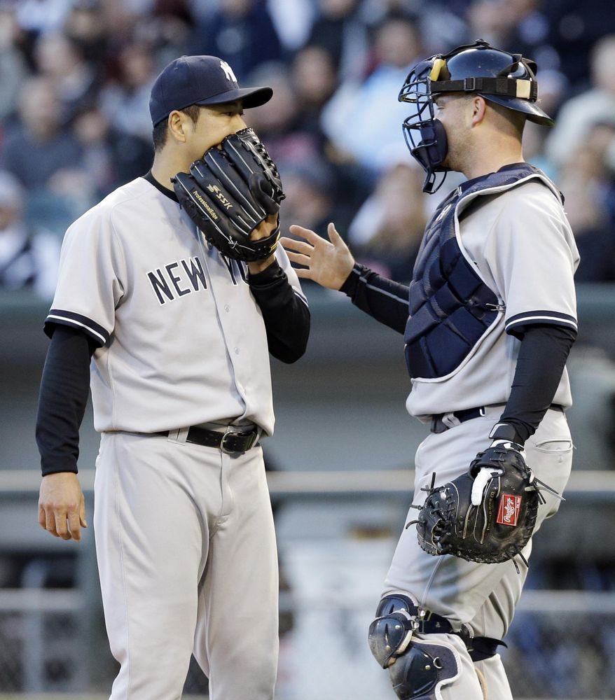 New York Yankees starter Hiroki Kuroda, left, of Japan, talks with catcher Brian McCann during the first inning of a baseball game against the Chicago White Sox in Chicago on Friday, May 23, 2014. (AP Photo/Nam Y. Huh)