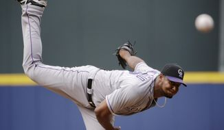 Colorado Rockies starting pitcher Juan Nicasio throws in the first inning of a baseball game against the Atlanta Braves, Saturday, May 24, 2014, in Atlanta. (AP Photo/David Goldman)