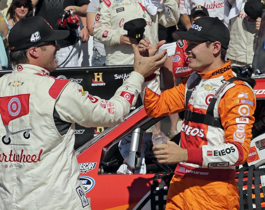 Kyle Larson, right, is congratulated by crew chief Scott Zipadelli, left, after winning the NASCAR Nationwide series History 300 auto race at Charlotte Motor Speedway in Concord, N.C., Saturday, May 24, 2014. (AP Photo/Chuck Burton)